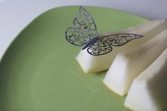 Juicy slices of melon lie on a green plate. On them is a decoration, a butterfly cut from a foil. Stock Images