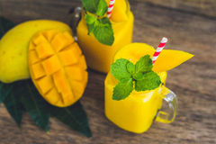 Juicy smoothie from mango in two glass mason jars with striped r Royalty Free Stock Image