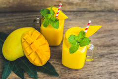 Juicy smoothie from mango in two glass mason jars with striped r Stock Photos