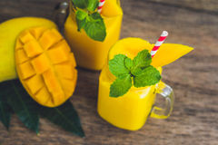Juicy smoothie from mango in two glass mason jars with striped r Stock Image