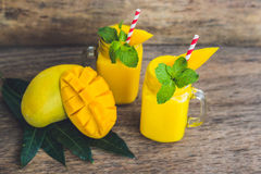 Juicy smoothie from mango in two glass mason jars with striped r Royalty Free Stock Photo