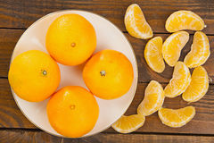 Juicy Spanish mandarins on plate on wooden background Royalty Free Stock Image