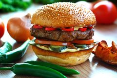Juicy, spicy burger with beef and red pepper, on a table with vegetables. Side view royalty free stock photos