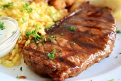 Juicy steak. With bbq sauce on a plate together with yellow rice, lemon, and parsley