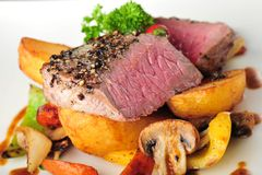 Juicy steak with baked potatoes and chilli Royalty Free Stock Image