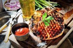 Juicy steak on the board, beer, ketchup and greens, vintage knife and fork. Juicy steak on the board, beer, ketchup and greens stock image