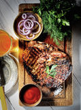 Juicy steak on the board, beer, ketchup, onion, parsley and dill, vintage knife and fork. Juicy steak on the board, beer, ketchup and greens stock photos