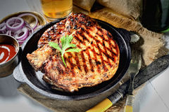 Juicy steak in a frying pan, onions and beer, napkin, vintage knife and fork. Juicy steak in a frying pan, onions and beer, vintage knife and fork royalty free stock image