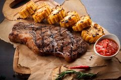 Juicy steak on the grill With rosemary, garlic, chili and corn on the grill and bread on the wooden board royalty free stock images