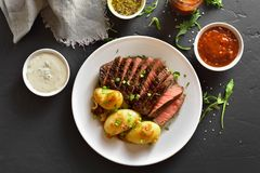 Steak medium rare beef with baked potatoes. Juicy steak medium rare beef with baked potatoes on white plate over black stone table. Top view, flat lay stock images
