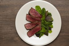 Juicy steak medium rare beef with green salad and tomatoes stock photography