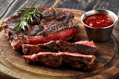 Juicy steak medium rare beef with spices on wooden board on table. Dry aged. Served with tomato sauce. Still life royalty free stock image