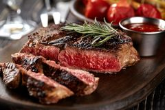 Juicy steak medium rare beef with spices on wooden board on table. Dry aged. Served with potatoes and tomato sauce. Still life royalty free stock photos