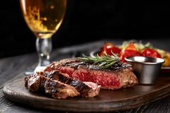 Juicy steak medium rare beef with spices on wooden board on table. Dry aged. Served with potatoes, beer, and tomato sauce. Still life stock photos