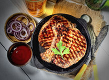 Juicy steak with parsley in a frying pan, onions, beer, vintage knife and fork, a napkin on a gray background. Juicy steak in a frying pan, onions and beer stock photography