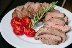 Juicy steak on the plate with tomatoes Royalty Free Stock Image