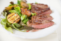A juicy steak with potato wedges Royalty Free Stock Images