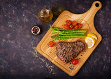 Juicy steak rare beef with spices on a wooden board and garnish of asparagus. Flat lay. Top view Stock Photography
