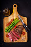 Juicy steak rare beef with spices on a wooden board and garnish of asparagus. Flat lay. Top view Stock Photo