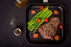 Juicy steak rare beef with spices on a wooden board and garnish of asparagus. Flat lay. Top view Stock Images