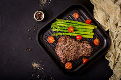 Juicy steak rare beef with spices on a wooden board and garnish of asparagus. Flat lay. Top view Stock Photos