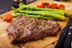 Juicy steak rare beef with spices on a wooden board and garnish. Of asparagus Stock Images