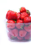 Juicy strawberries in a container. Juicy, ripe strawberries in a plastic container on a white background. Partly in the frame, closeup Stock Photo