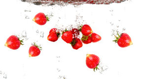 Juicy strawberries under water. Healthy and tasty foods on a white background royalty free stock photos