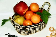 Basket with juicy and bright fruits. Juicy summer fruits in a basket lie next to various objects royalty free stock image