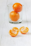 Juicy tangerines in glass. On a white wooden surface Royalty Free Stock Images