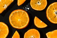 Juicy tangerines, sliced on a black background stock photography