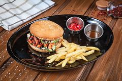 Juicy and tasty burger with fish and vegetables served on black plate with french fries. American fastfood. Fishburger with copy stock photos
