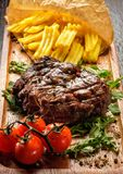 Juicy tasty grilled fillet steak served with tomatoes and French Stock Photos