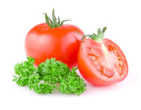 Juicy tomato cut in half and a sprig of parsley Royalty Free Stock Image