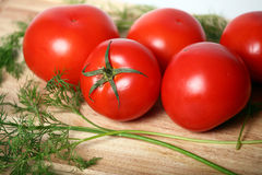Juicy tomatoes. Tomatoes for salad on a kitchen table. Near to tomatoes very useful greens Stock Photography