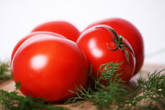 Juicy tomatoes. Tomatoes for salad on a kitchen table. Near to tomatoes very useful greens Stock Photos