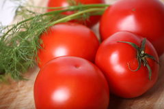 Juicy tomatoes. Tomatoes for salad on a kitchen table. Near to tomatoes very useful greens Royalty Free Stock Photos