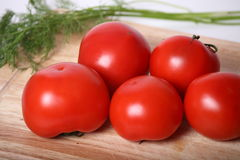 Juicy tomatoes. Tomatoes for salad on a kitchen table. Near to tomatoes very useful greens Stock Image