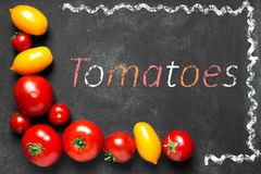 Juicy tomatoes on the black chalkboard Stock Images