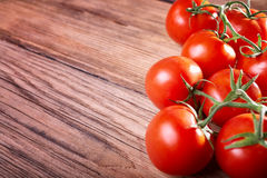 Juicy tomatoes on a wooden table Royalty Free Stock Photos