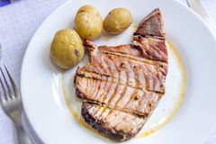 Tuna steak with potatoes served on white plate. Juicy tuna steak with potatoes served on white plate Stock Photography