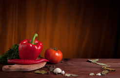 Juicy vegetables, herbs and spices on dark wood. Juicy red pepper,  tomato, herbs and spices on dark wood table Royalty Free Stock Image
