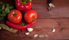 Juicy vegetables, herbs and spices on dark wood. Juicy red pepper,  tomato, herbs and spices on dark wood table Royalty Free Stock Images