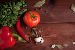 Juicy vegetables, herbs and spices on dark wood. Juicy red pepper,  tomato, herbs and spices on dark wood table Stock Photography