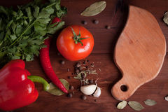Juicy vegetables and spices on a wood table with cutting board. Red pepper, tomatoes and chili pepper on a wood table with herbs and spices and cutting board Royalty Free Stock Photos