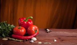 Juicy vegetables and spices on a wood table. Red pepper, tomatoes and chili pepper on a wood table with herbs and spices Royalty Free Stock Images