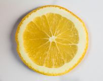 Juicy vibrant yellow orange slice closeup on white backing. Vibrant yellow orange slice closeup on white backing Stock Photo