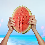 Juicy water-melon. Two pieces of ripe water-melon in hands, beach Stock Photography