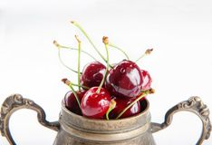 Juicy wet cherries in brass vessel stock images