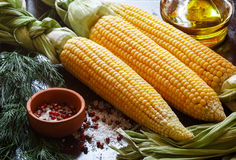 Juicy young corn ready for baking with olive oil and spices Stock Photo